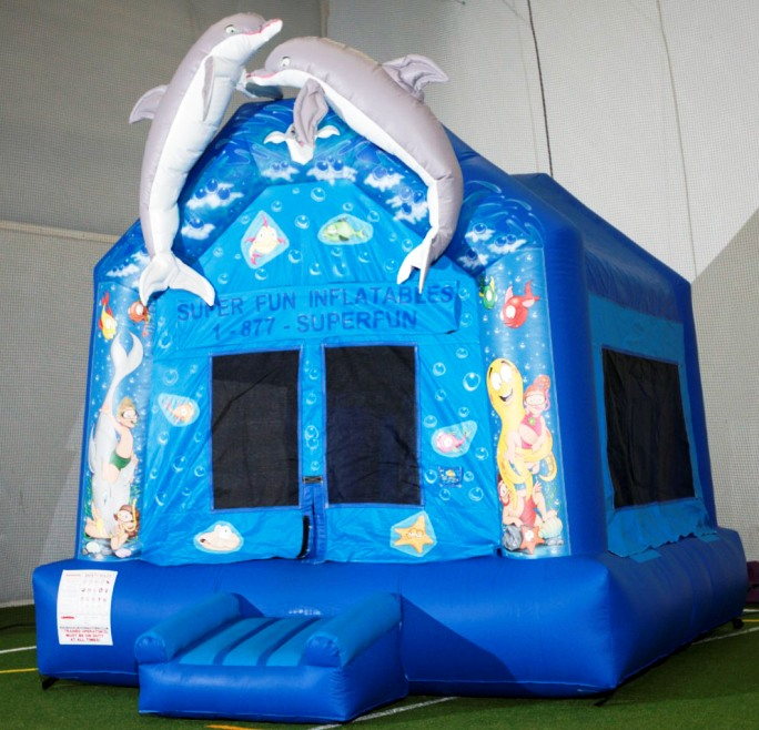 blue inflatable bounce house with dophins on top